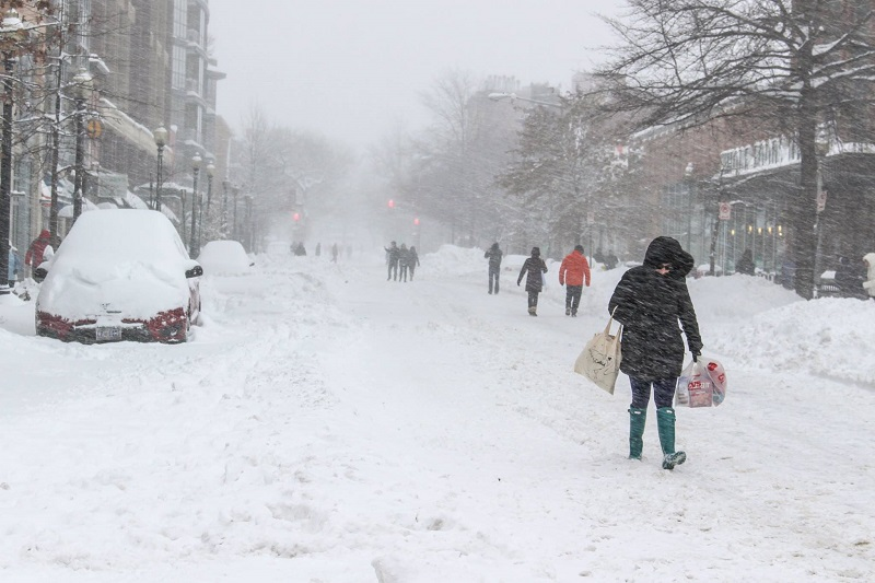 people walking on the street as it snows