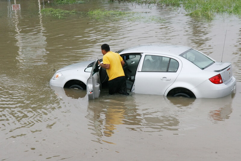 man pushing his car through flood waters