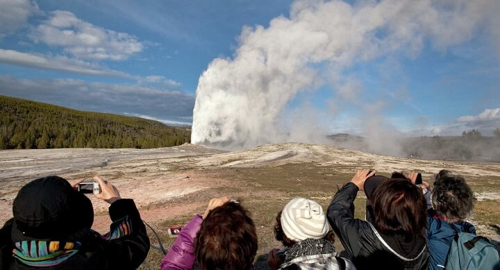 Tourists photograph Old Faithful erupting at Yellowstone National Park in Montana.