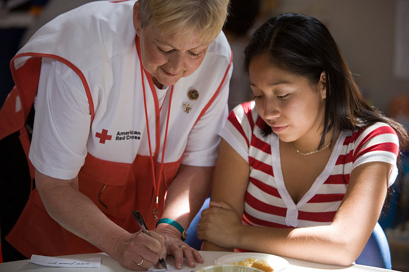 red cross volunteer with disaster victim filling out paperwork