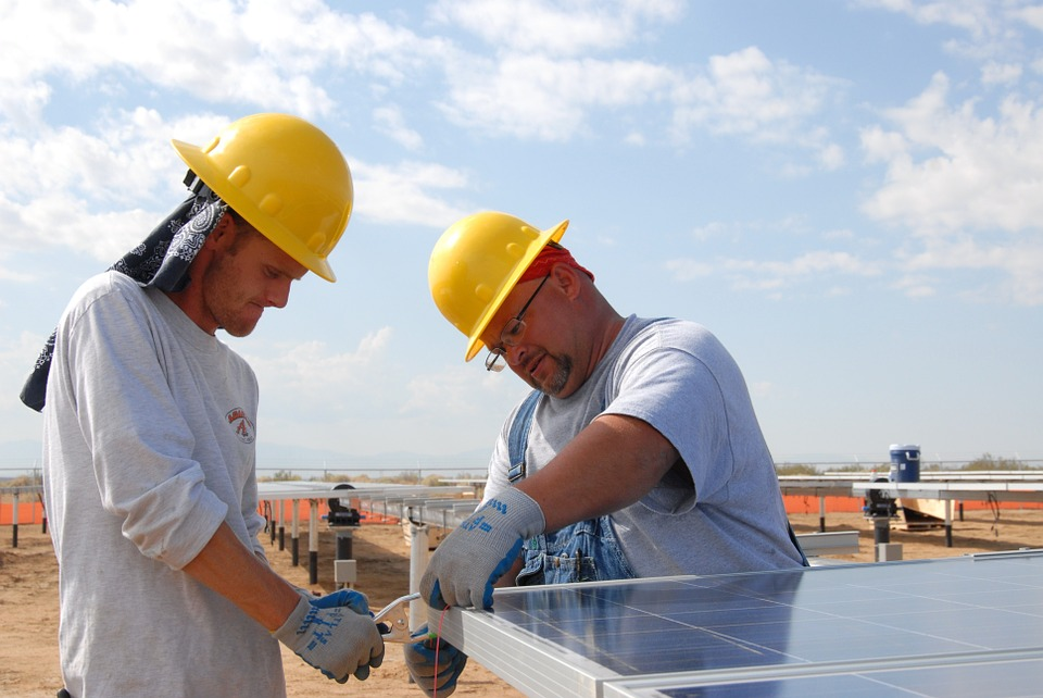 two men in yellow hard hats working on a solar panel