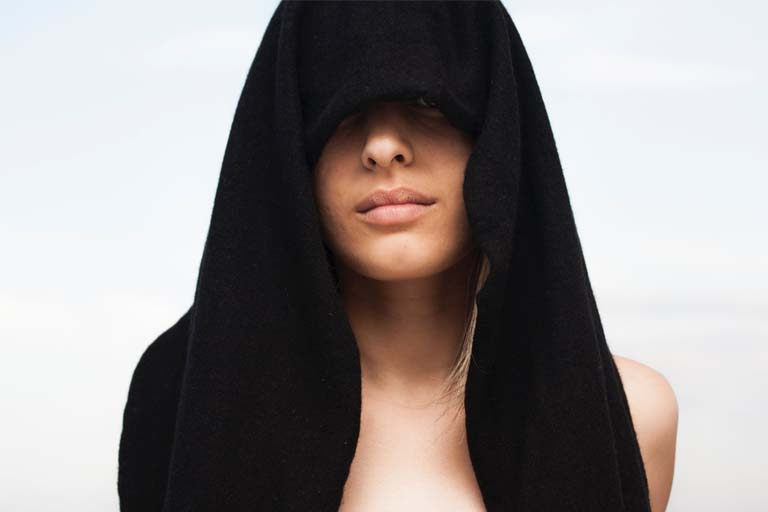 lady with a black cloth covering her hair and eyes