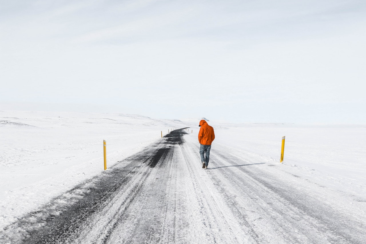 person walking at road covered in snow