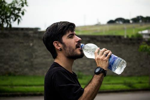 Man wearing black shirt drinking water